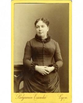 Jeune femme en robe debout, mains croisées