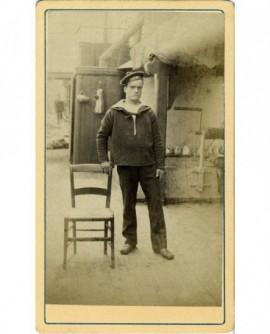 Marin debout, appuyé sur uen chaise
