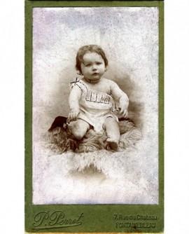 Bébé en chemise assis sur une peau