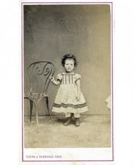 Fillette debout en robe, appuyée à une chaise