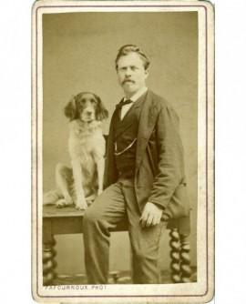 Homme assis sur une table avec son chien
