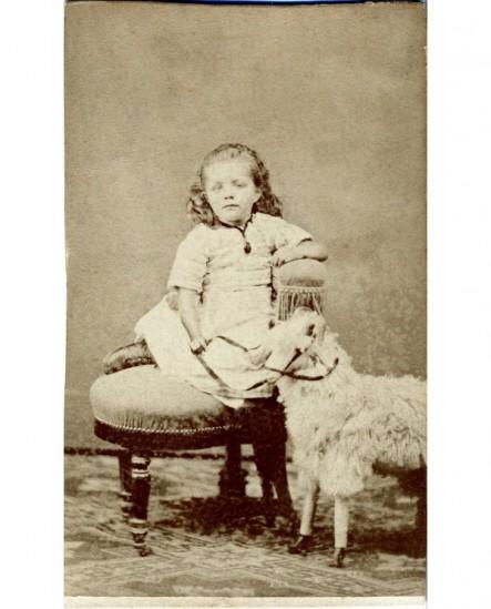 Fillette assise à coté d'un mouton