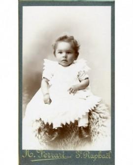 Bébé en robe assis
