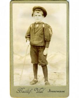Enfant en costume marin, sac au dos,une canne à la main