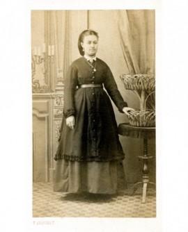 Jeune femme en robe debout, appuyée sur une table