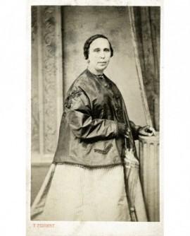 Femme en robe et veste debout, son ombrelle à la main
