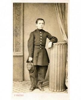 collégien en uniforme accoudé à une colonne, casquette à la main
