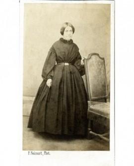 Femme debout en robe, appuyée à une chaise