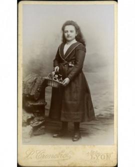 Jeune fille aux longs cheveux, portant un panier de fleurs