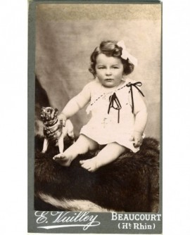 Fillette en chemise, épaule dénudée, assise avec un jouet (chien)