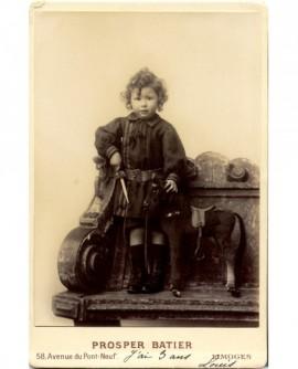 Garçonnet en robe, debout sur un banc, son cheval à roulettes près de lui