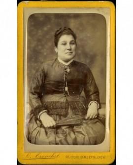 Femme assise, tenant son éventail sur les genoux