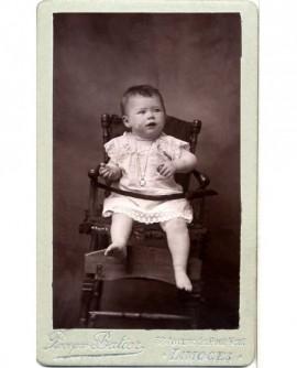 Bébé en chemise, assis dans sa chaise, retenu par un ruban