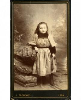 Petite fille en robe, sa corde à sauter à la main