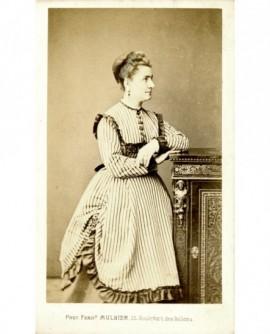 Femme en robe à rayures debout de profil, appuyée sur un meuble