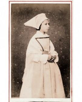 Jeune fille habillée en blanc tenant un livre contre elle