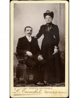 Couple (homme moustachu assis, femme debout s'appuyant sur lui)
