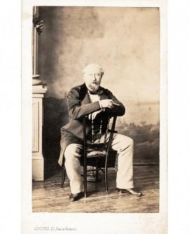 Homme barbu assis à califourchon sur une chaise, cigare à la main
