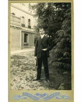 Homme debout, son panama à la main, posant devant un hôtel particulier