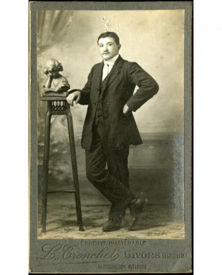 Jeune homme debout, pieds croisés, accoudé à une sellette