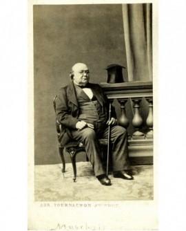 Homme chauve en lorgons assis avec gants et canne (Marchais)