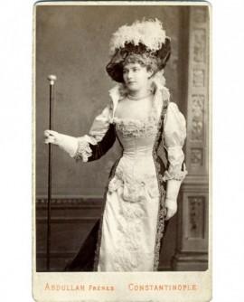 Femme très mince debout en robe avec chapeau et canne