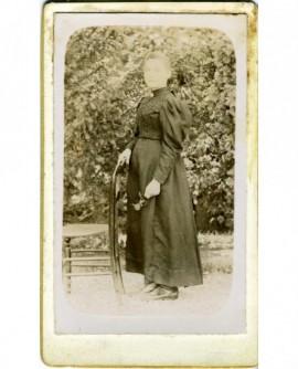 Femme debout en robe, appuyée sur une chaise, une rose à la main