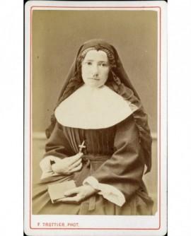 Religieuse assise, tenant son crucifix d'une main, un livre de l'autre