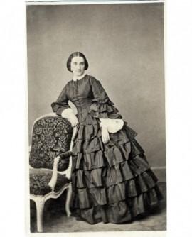 Femme en robe à plis debout, accoudée à une chaise