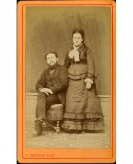 Couple (homme barbu, femme debout la main sur chaise)