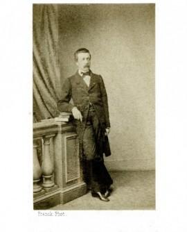 Homme moustachu debout, accoudé à une balustrade