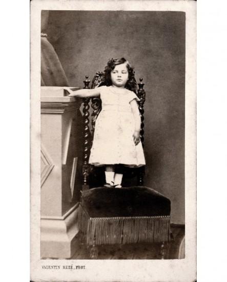 Fillette en robe blanche debout sur une chaise