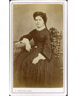 Jeune fille assise, accoudée à une table