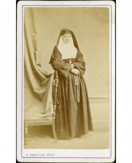 Religieuse contre une chaise, chapelet en main droite