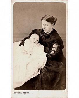 Jeune femme en noir tenant un bébé en robe (de baptême)