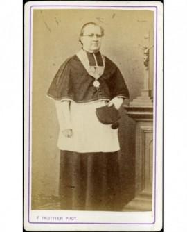 Ecclésiastique à lunettes (chanoine en camail, sa barrette à la main)
