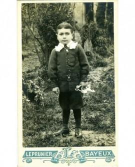 Jeune garçon debout, petit cheval à roulette à la main (jouet)
