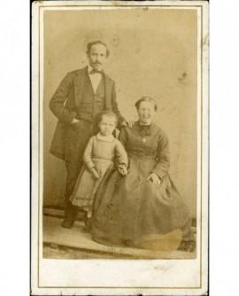 Photo de famille (père debout, mère assise, fillette entre eux)