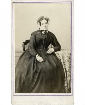 Femme en robe et bonnet assise