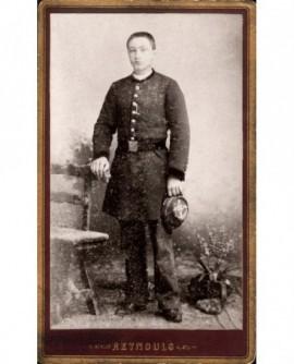 Lycéen en uniforme, sa casquette à la main.