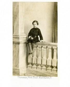 Jeune garçon en uniforme à ceinturon, assis sur une balustrade