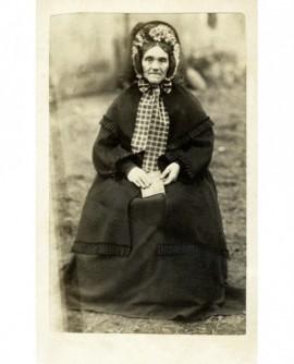 Femme en robe et en capote à fleurs assise, un livre à la main