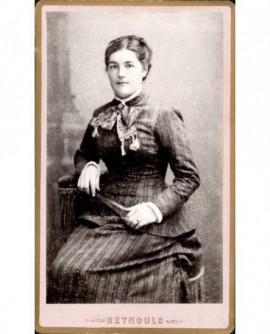 Jeune femme assise tenant son éventail