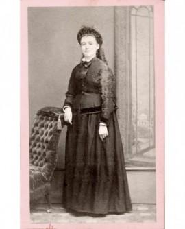 Femme coiffée d'un chapeau appuyée sur un fauteuil