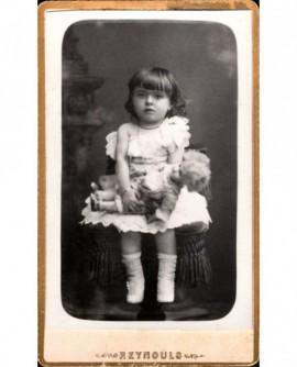 Fillette en robe blanche tenant une poupée de porcelaine