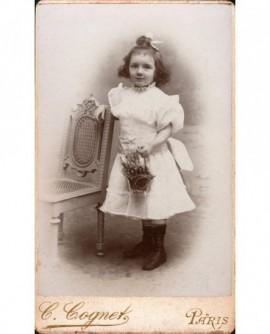 Fillette en robe blanche, panier à la main, appuyée sur une chaise