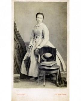 Femme en robe ombrelle à la main, accoudée à une chaise