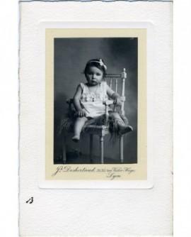 Bébé en chemise assis sur une chaise