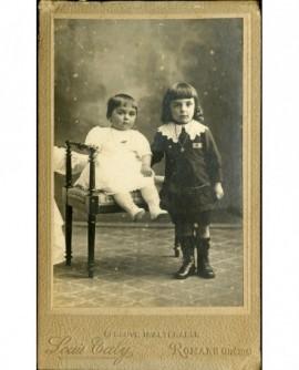 Deux jeunes enfants (l'aîné debout, le plus jeune assis)