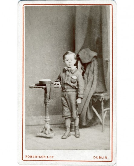 Garçon debout chapeau à ruban sur un guéridon